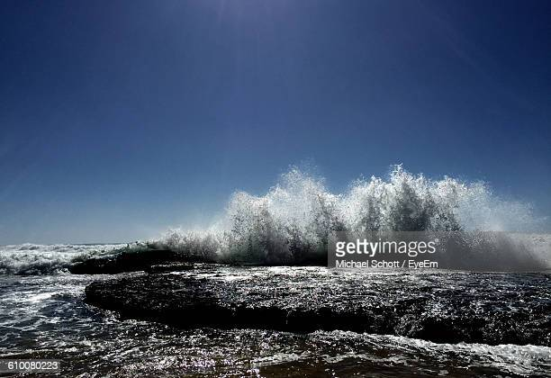 Water Splashing On Rocks Against Clear Blue Sky During Sunny Day