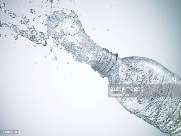 Water splashing out of bottle, close-up