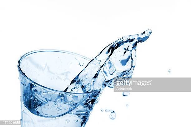 water splashing out the top of a clear glass - glass of water stock pictures, royalty-free photos & images
