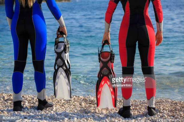 Water sportteam. Mooie duiker, twee aantrekkelijke, vitale, rijpe vrouwen. klaar om te gaan duiken of snorkelen. Gekleed in een wetsuit. Lang blond haar, mooie blauwe ogen. Sportieve vrouwen. Mooie blauwe zee op de achtergrond.