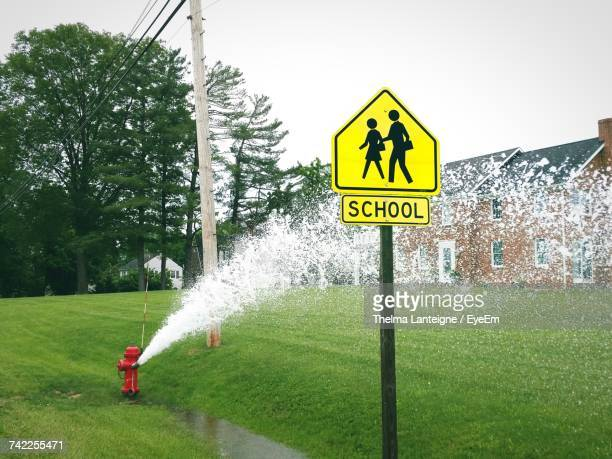 Water Spraying From Fire Hydrant By School Sign