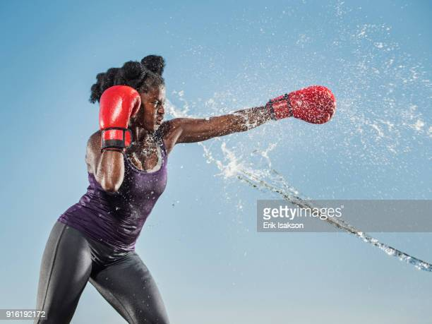 Water spraying on black woman boxing
