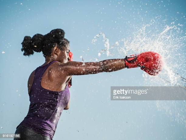 water spraying on black woman boxing - impact stock pictures, royalty-free photos & images