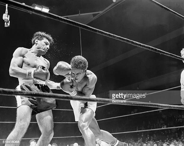 Water sprays from the head of Eduardo Lausse as he lands a hard left to the body of Milo Savage, Salt Lake City middleweight, during the fourth round...