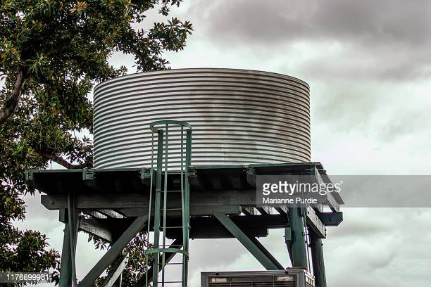 water storage tank on an elevated stand - water tower storage tank stock pictures, royalty-free photos & images