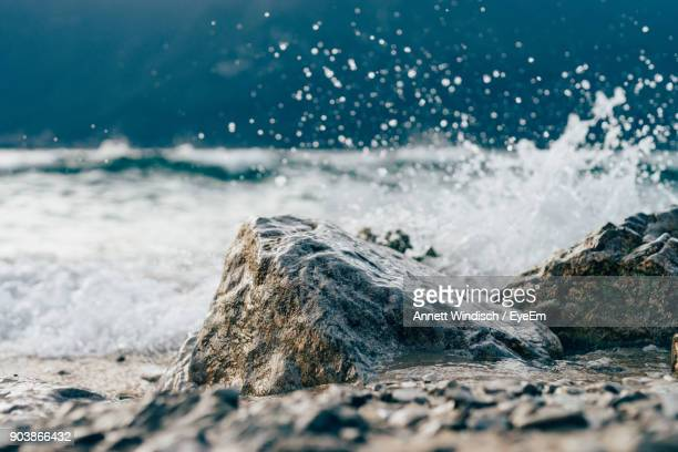 water surface view of wave splashing on rocks in sea - rocha imagens e fotografias de stock