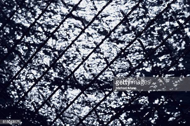 Water surface viewed through wire mesh fence