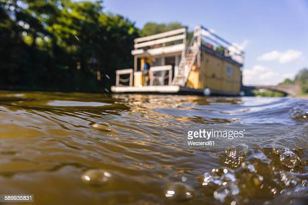 water surface with house boat in background - houseboat stock pictures, royalty-free photos & images