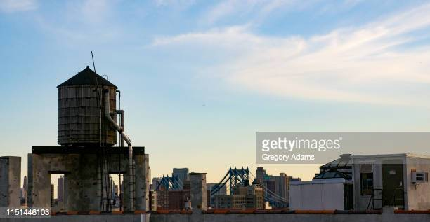 a water tank on the top of a building in new york city - water tower storage tank stock pictures, royalty-free photos & images