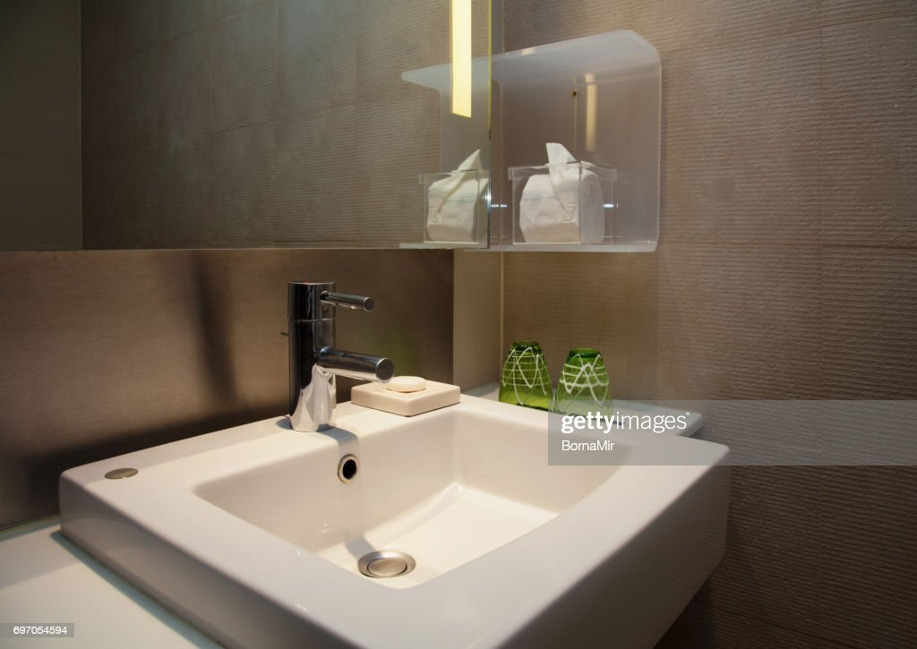 Water Tap And Ceramic White Sink In A Modern Wc With Brown Tiles ...