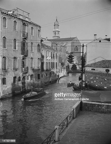 A water taxi and a rowing boat crossing the canal and passing below the traffic light Venice 1951