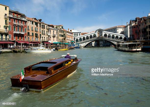 CONTENT] A water taxi navigates the busy Grand Canal heading to the Rialto Bridge