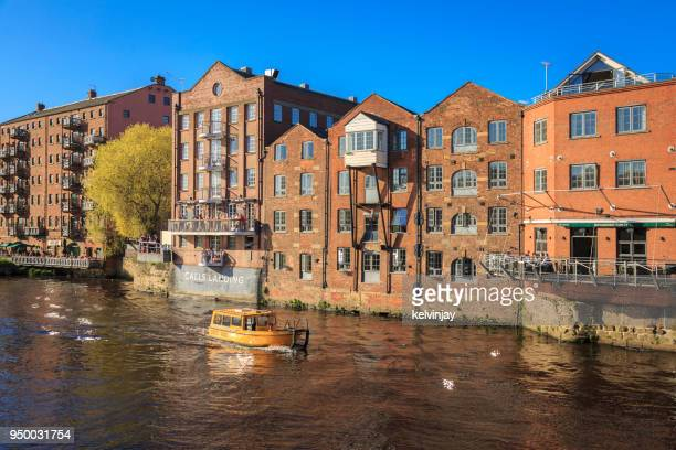 water taxi passing apartments on the river aire in leeds, yorkshire. - leeds stock pictures, royalty-free photos & images