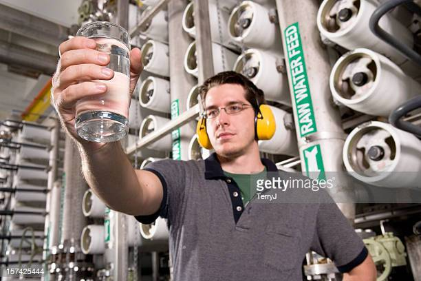 water technician inspects water at public utility plant - sewer stock pictures, royalty-free photos & images