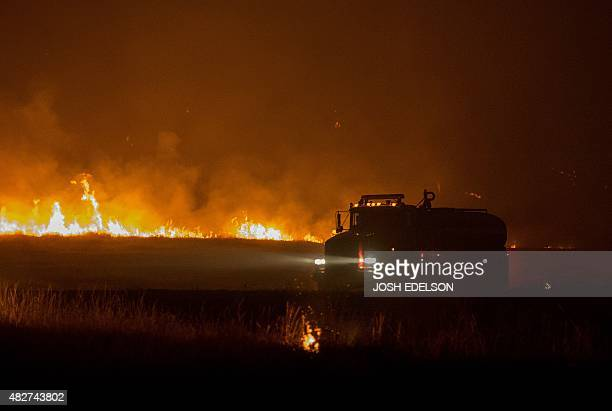 A water tender drives near flames from the Rocky fire near Clear Lake California on August 2 2015 The fire has charred more than 27000 acres and is...