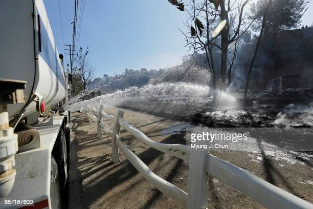 A water tender wets down smoldering remnants of tires on Wentworth Street in SunlandTujunga in the aftermath of the Creek fire on December 6 2017 in...
