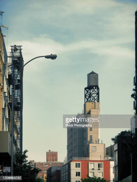 water tower on rooftop of building in noho, manhattan, new york city - manhattan new york city stock pictures, royalty-free photos & images