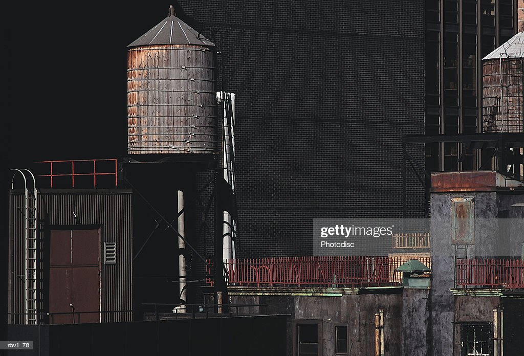 water towers rise above warehouse buildings on roofs next to larger buildings : Foto de stock