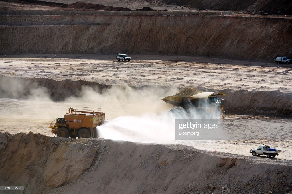 A water truck, left, sprays water onto the open-pit mine as a dump truck loaded with ore drives past at the Norton Gold Fields Ltd. Enterprise operations 68 kilometers north-west of Kalgoorlie, Australia, on Wednesday, Aug. 7, 2013. Norton, the Australian producer controlled by China's Zijin Mining Group Co., is seeking further acquisition targets as falling prices cut the value of mines. Photographer: Carla Gottgens/Bloomberg via Getty Images