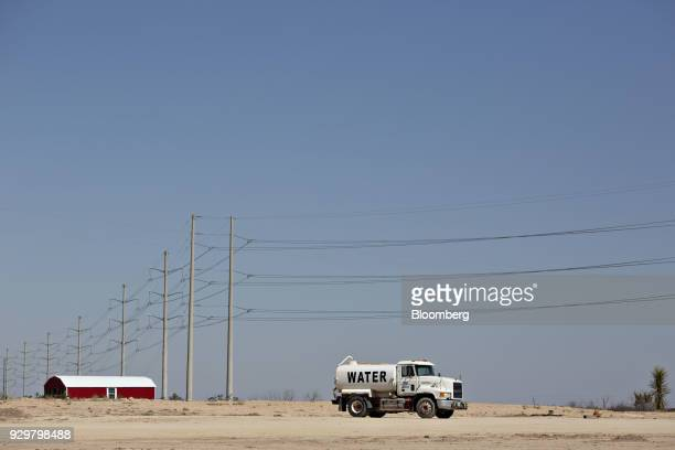A water truck sits parked on a rural road in the Permian Basin outside Crane Texas US on Friday March 2 2018 Chevron the world's thirdlargest...