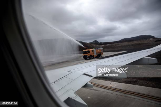 A water truck sprays water to celebrate the first inaugural commercial plane from Johannesburg after it landed at the newly built Saint Helena...