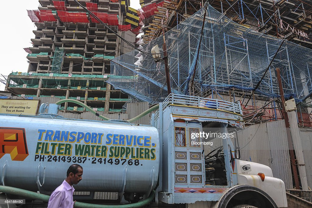 A water truck stands outside a luxury residential tower under construction at a site developed by Omkar Realtors & Developers Pvt. in the Parel area of Mumbai, India, on Friday, Aug. 8, 2014. Omkar is playing an important role in Mumbais plan to do something about its enormous and embarrassing problem: at least 6.5 million slum dwellers, still living without running water, private toilets or the basics of sanitation. Omkar's Cresent Bay development consists of six luxury towers with million-dollar apartments overlooking the Arabian Sea, coupled with housing blocks nearby with free homes for all the slum dwellers with rights to the land. Photographer: Dhiraj Singh/Bloomberg via Getty Images