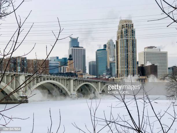 Water vapor rises above St Anthony Falls on the Mississippi River beneath the Stone Arch Bridge during frigid temperatures on January 31 2019 in...