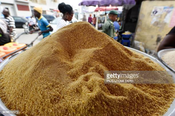 A water vendor pushes his cart past a tray of garri on sale in the Obalande district of Lagos on January 24 2018 The government of Anambra State in...