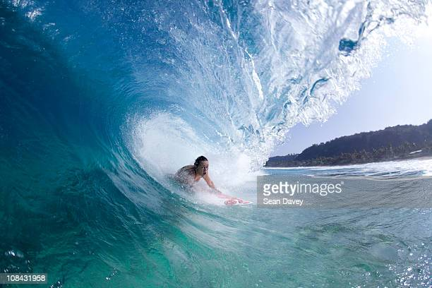 A water view of a surfer girl in the tube, in Hawaii.