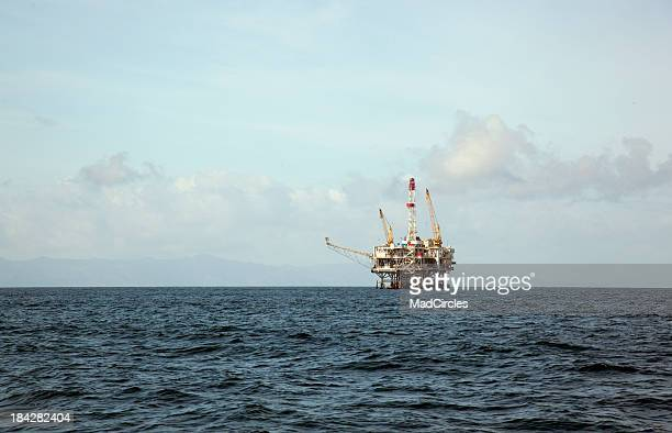 Water view of an offshore oil rip in the middle of the ocean