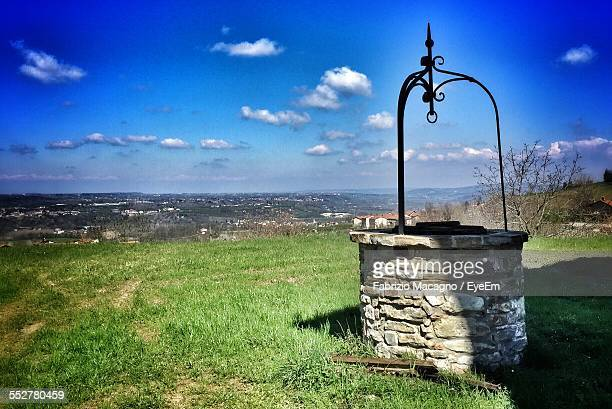 Water Well On Amidst Grassy Field Against Blue Sky