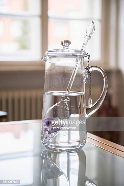 Water with gemstones in pitcher in kitchen