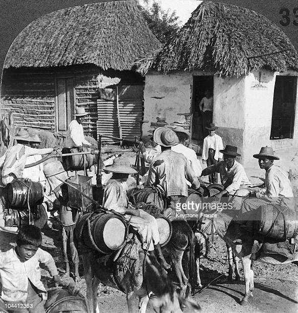 Watercarriers on donkeys in Baranquilla Columbia around 19001920 Rustic houses with straw roofs can be seen The barrels were filled at the well...