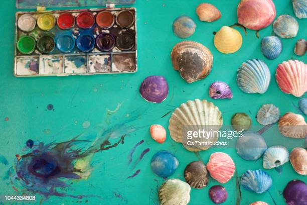 watercolor painted sea shells over a green stained background - emerald green stock pictures, royalty-free photos & images