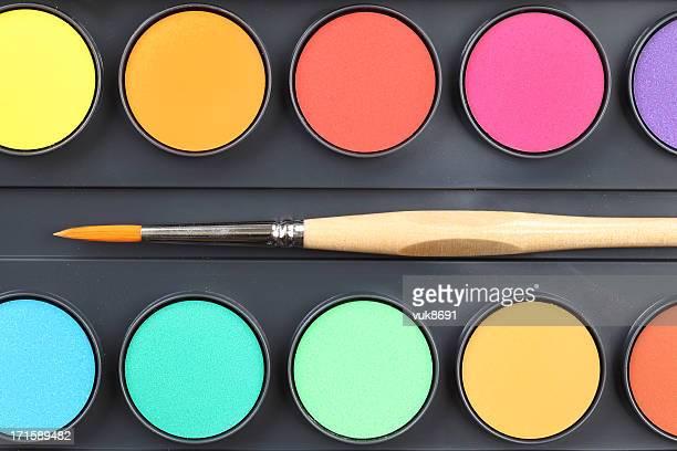 Watercolor paints and paintbrush