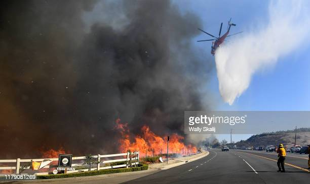 A waterdropping helicopter passes makes a drop along Madera Road as the Easy Fire burns in Simi Valley California on Ocotober 30 2019
