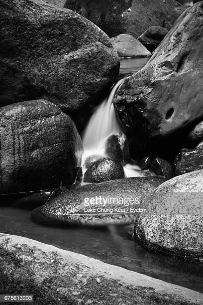 Waterfall Amidst Rocks In Forest