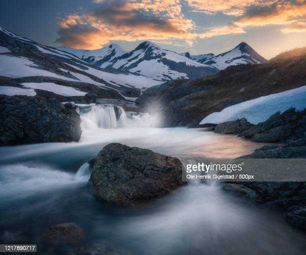 waterfall amidst snowcapped mountains - scandinavia stock pictures, royalty-free photos & images