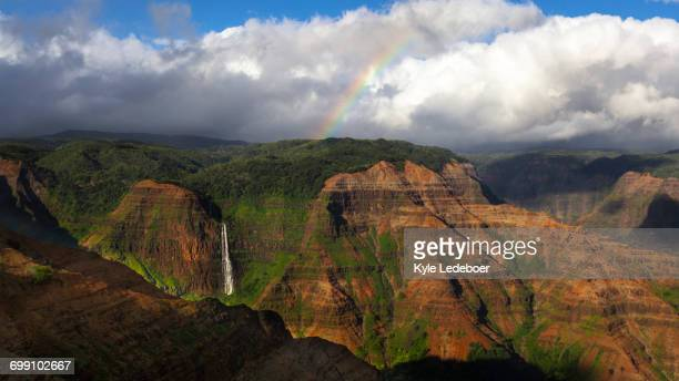 waterfall and a rainbow, looking out across wiamea canyon, kauai - waimea canyon stock pictures, royalty-free photos & images