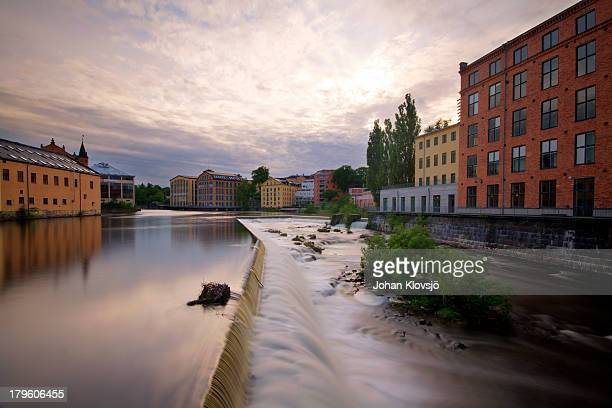 waterfall and houses in norrköping industrial area - norrkoping fotografías e imágenes de stock