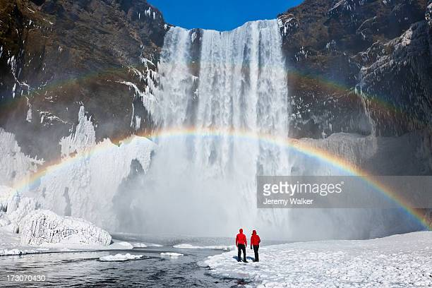 Waterfall and rainbow with couple