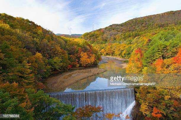 Waterfall and tree covered mountains in autumn. Hachimantai, Iwate Prefecture, Japan