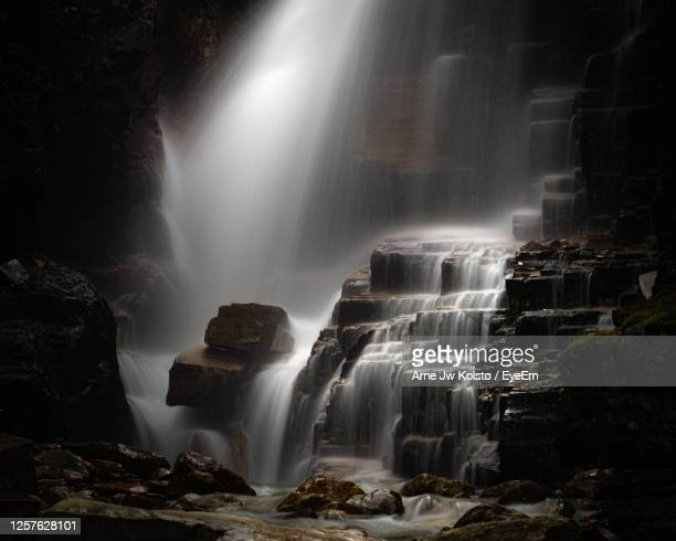 waterfall between cliffs in norwegian mountains - arne jw kolstø stock pictures, royalty-free photos & images