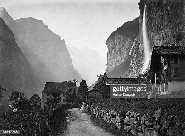 A waterfall cascades down the side of the rock face at a small mountain settlement in the Lauterbrunnen Valley