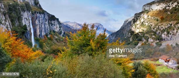 waterfall, cliffs and trees in collados del ason natural park under cloudy sky, cantabria, spain - cantabria fotografías e imágenes de stock