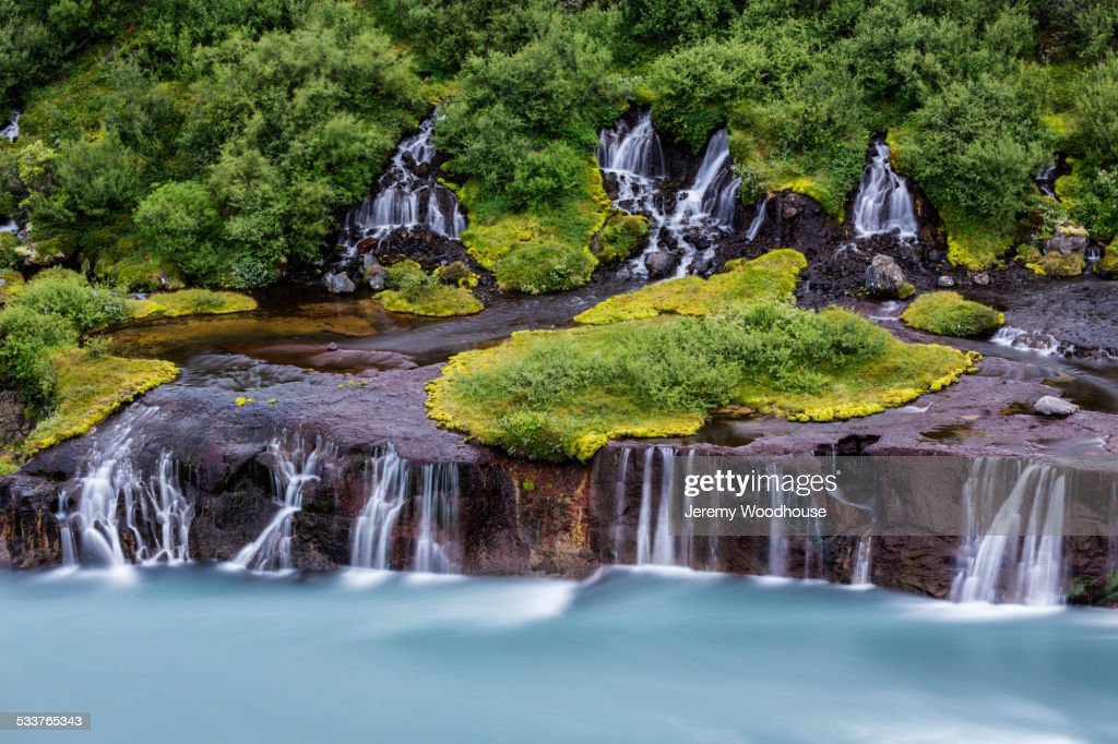 Waterfall flowing over rock formations to lake : Foto stock