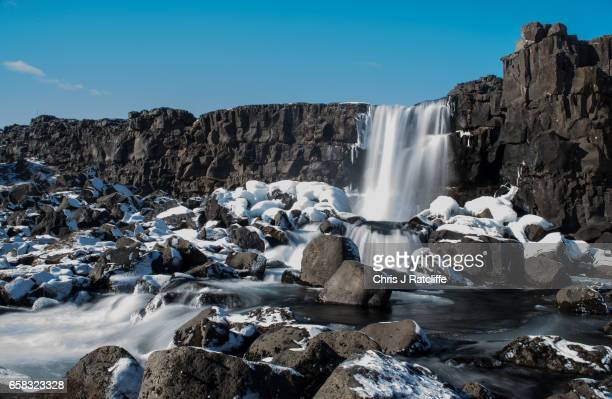 A waterfall flows over a tectonic plate rift on March 27 2017 at Pingvellir Iceland Iceland's economy has been booming after an economic crash and...