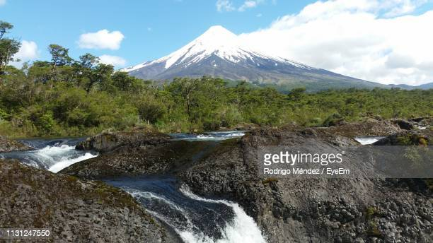 waterfall in forest with snowcapped mountain in background against sky - petrohue river stock photos and pictures