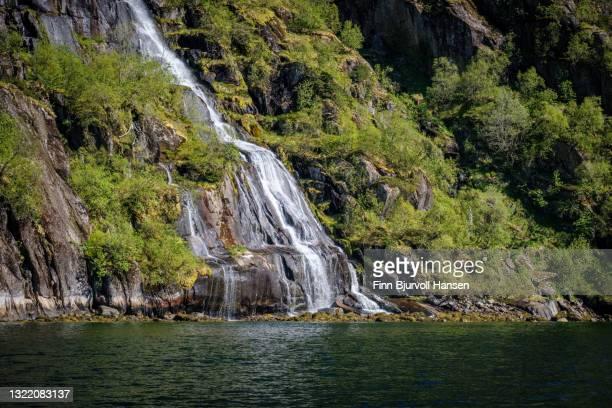 waterfall in trollfjord lofoten islands norway-portrait - finn bjurvoll foto e immagini stock