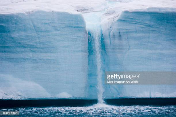 a waterfall is created by a melting iceberg, svalbard, norway - iceberg photos et images de collection